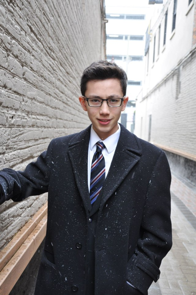 young man in black pea coat and tie in alley way, snow blowing, wearing glasses