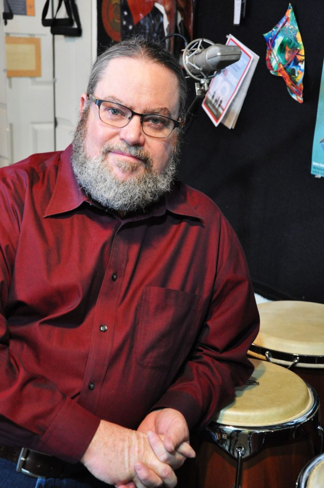 man sitting, leaning on drums, swearing long-sleeved red collar shirt