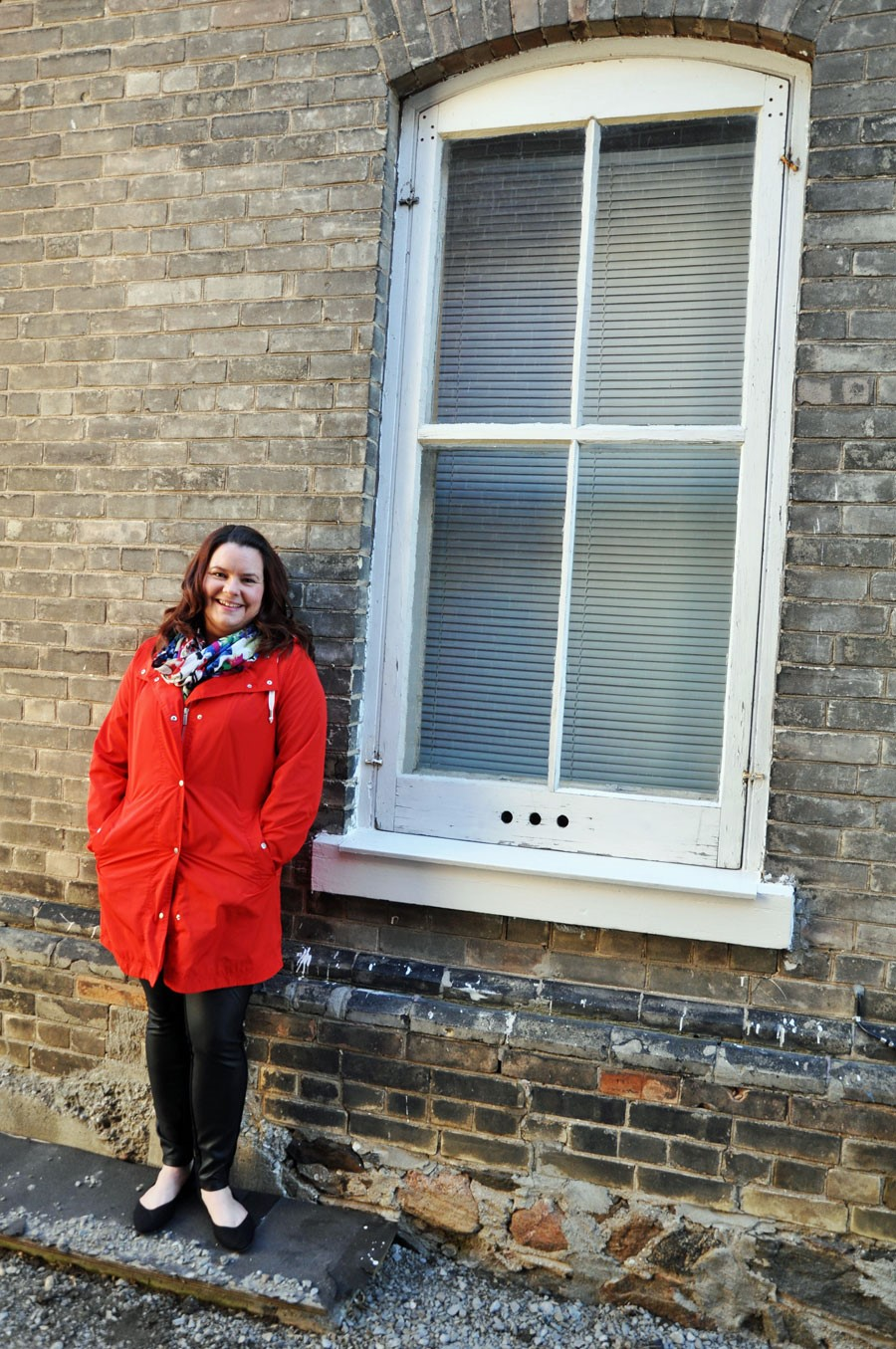 woman in red jacket leans against grey brick wall, big white window beside her