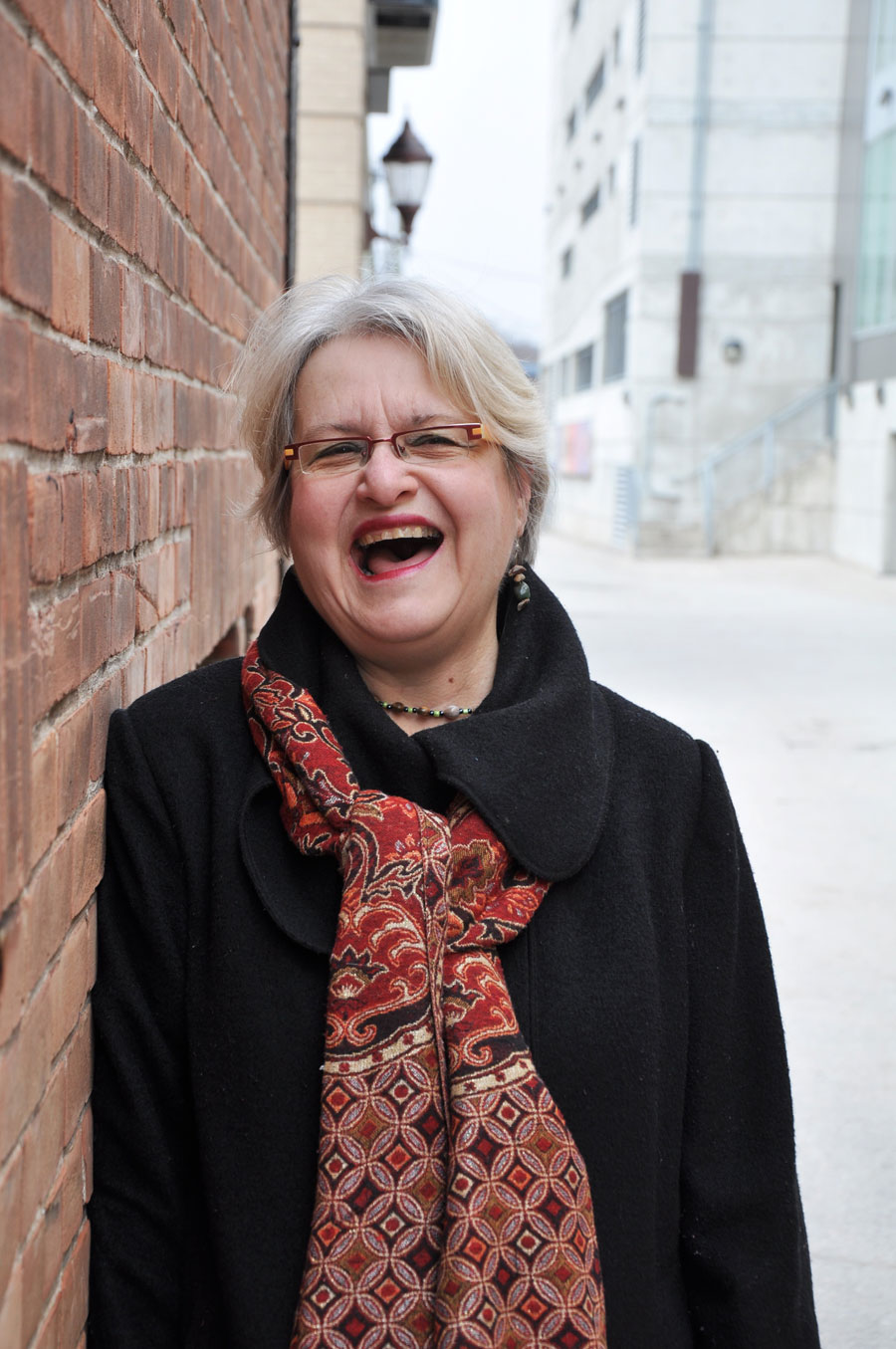 woman in black pea coat leaning against brick wall, laughing