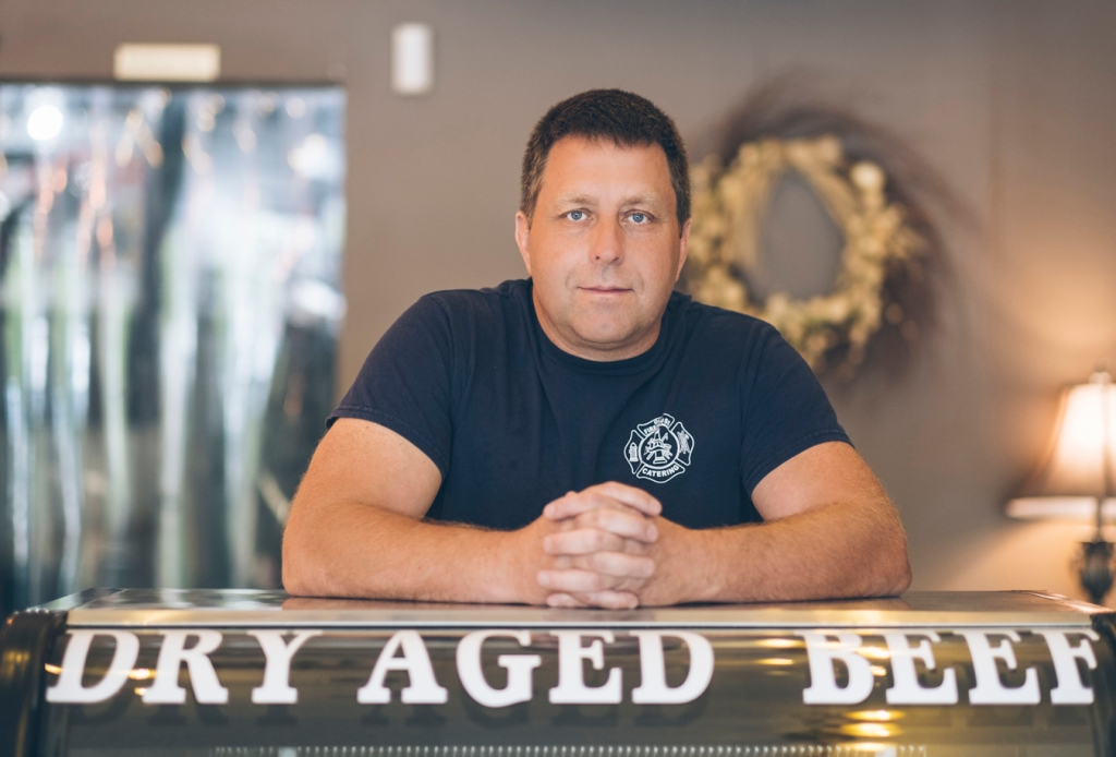 Man in firefighter navy T-shirt leaning on counter at meat shop