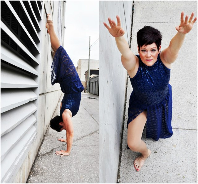 woman with dark hair, blue dress, one shot doing hand stand, another arms in air reaching for the sky, in a back alley