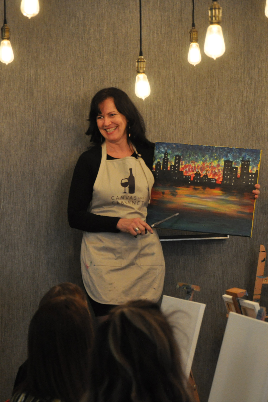 Woman teaching a painting class, canvas and brush in hand