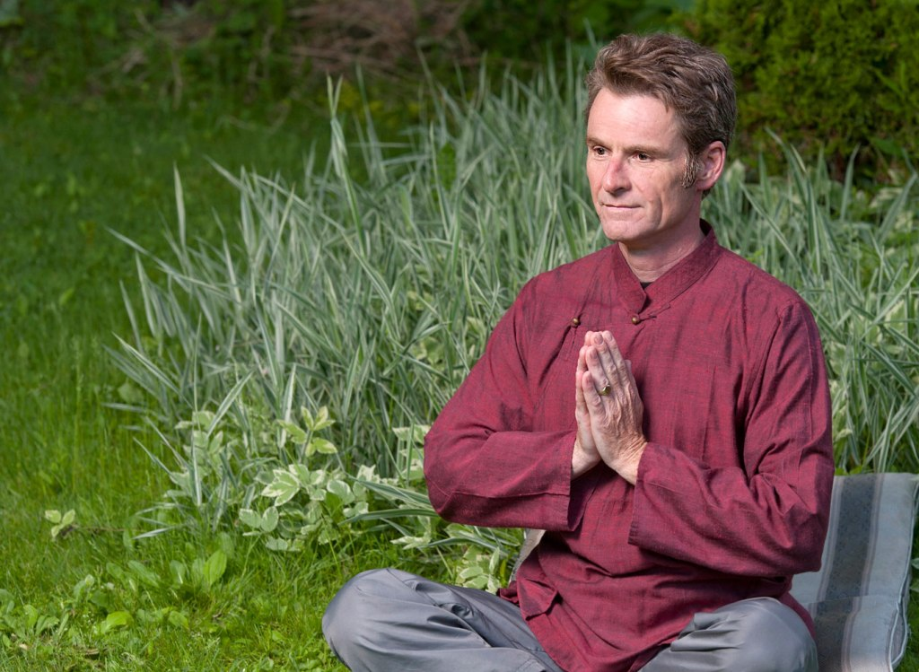 man in red long-sleeve top and grey pants meditating in a garden