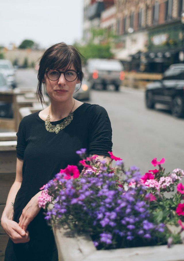 Woman in black top, glasses, downtown Barrie, leaning on flower pot