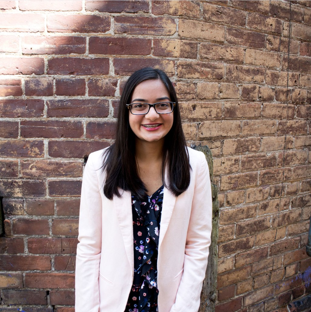 young woman with dark hair standing against brick, pink blazer