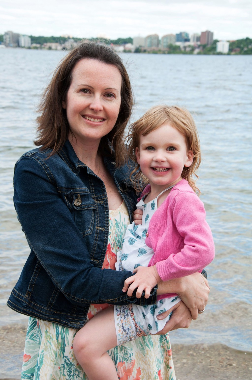 woman in jean jacket and dress, dark hair, holding her young daughter in pink sweater and dress, lake behind them