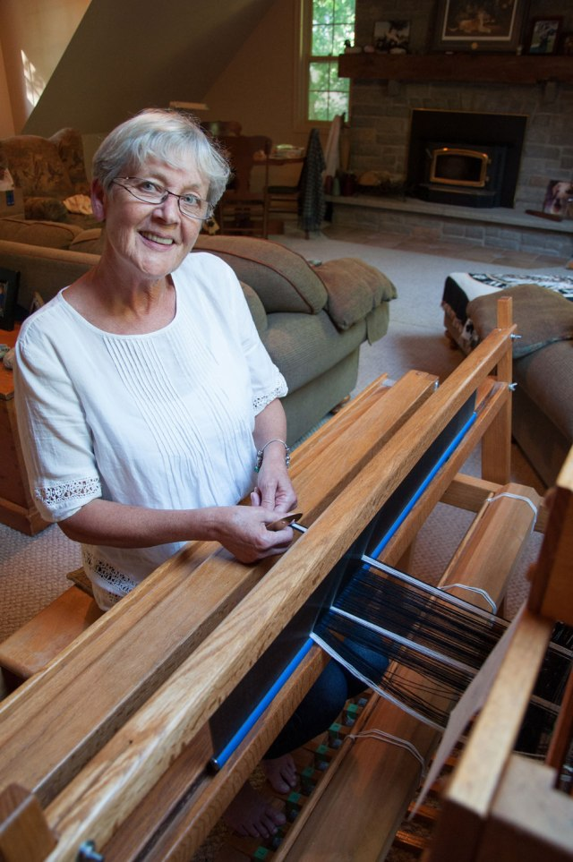 woman with grey hair and white shirt sitting at a loom