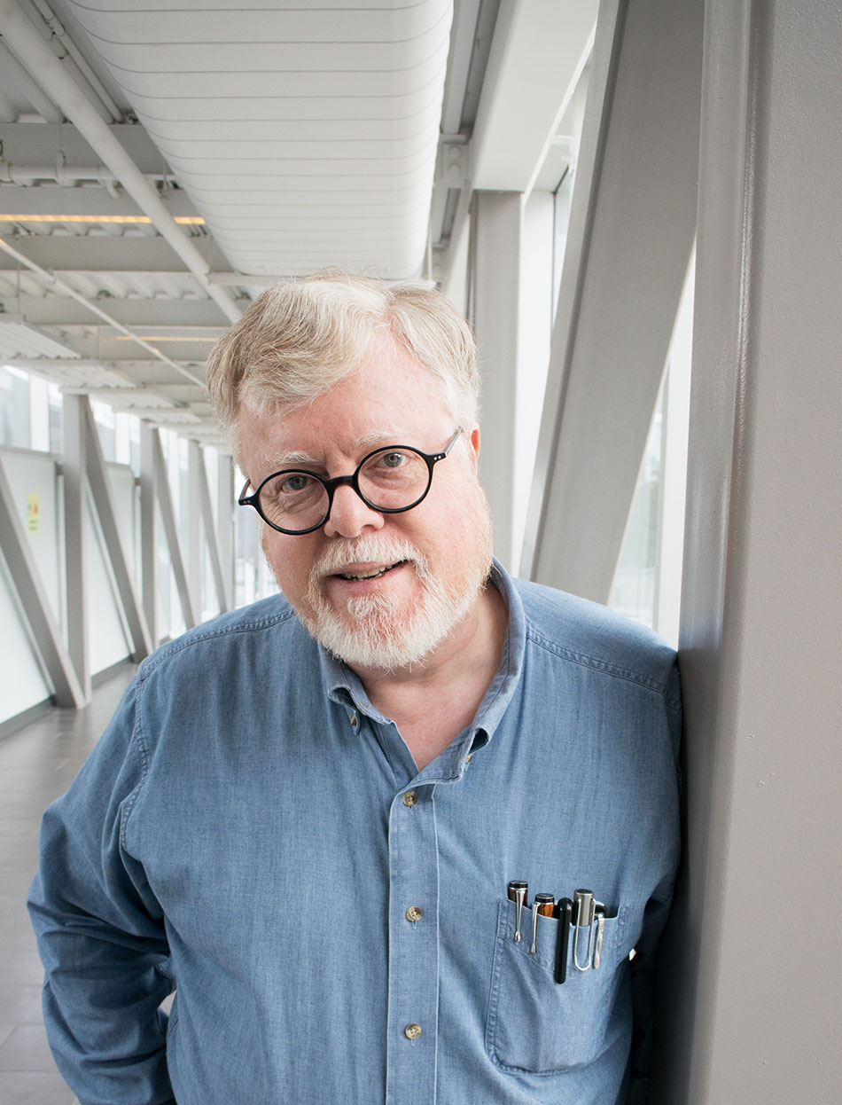 man with blue collared shirt, grey hair, black glasses, standing in well lit modern building