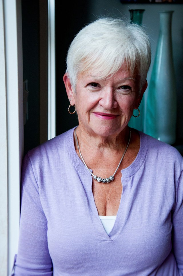 woman with white hair, purple top, standing near window in her house
