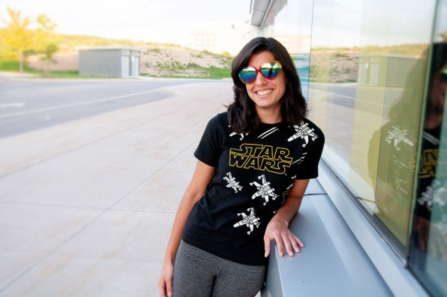 young woman wit star wars shirt on, heart-shaped funky sunglasses, leaning against window outside