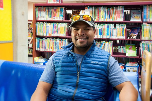 man with blue vest, wearing hat with sunglasses on it, sitting on blue chair in the library