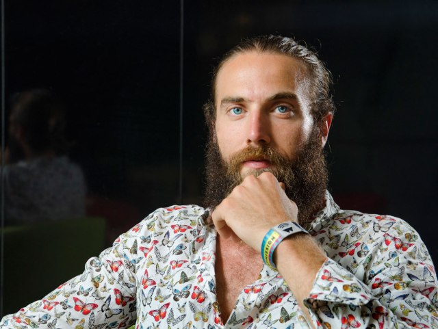 young man with big beard, wearing butterfly shirt