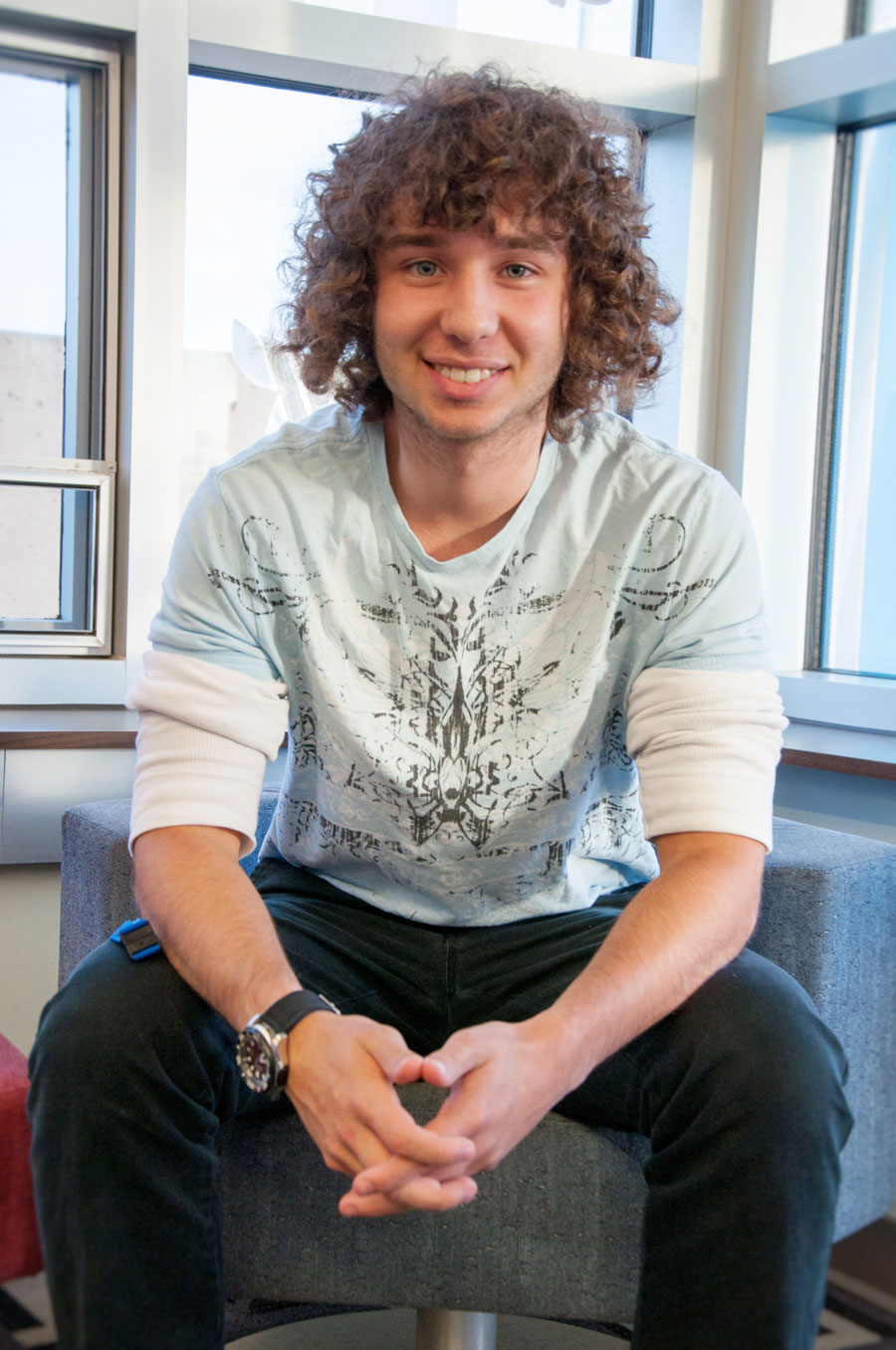 young man with curly hair sitting on chair, leaning forward, fingers interlocked