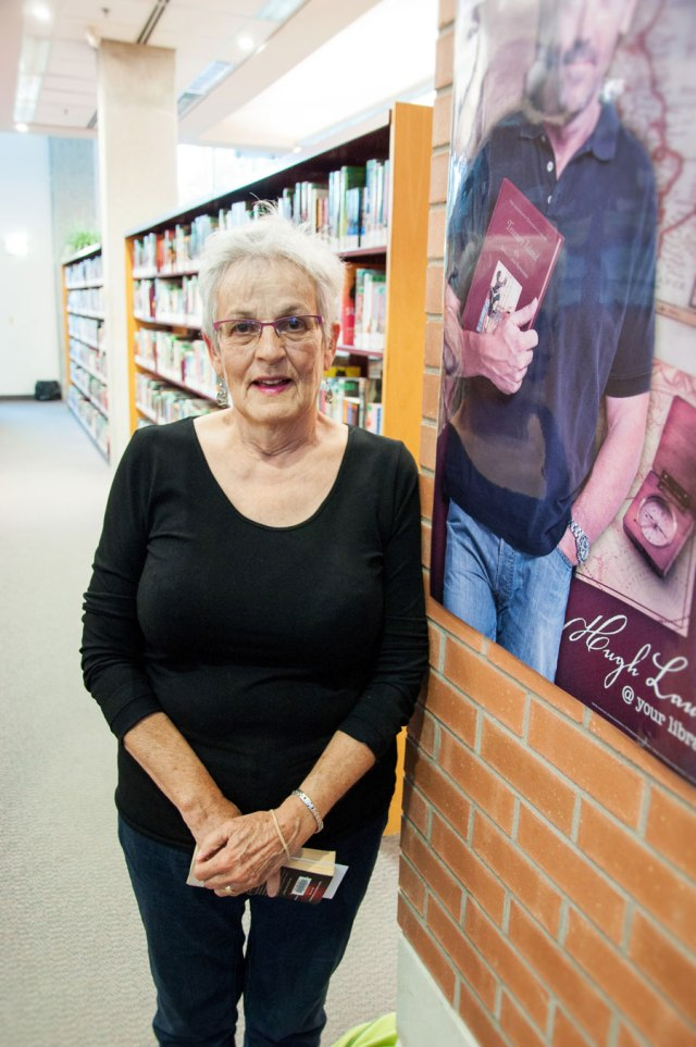 older woman with white hair, black top and jeans stands in a library