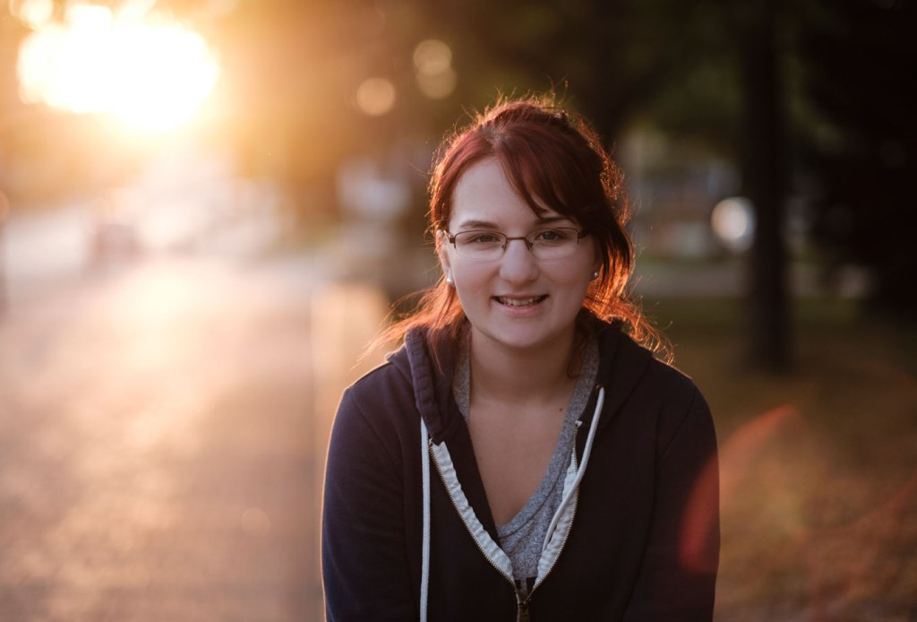 young woman at sunset, sweatshirt on, glasses, dark hair ponytail