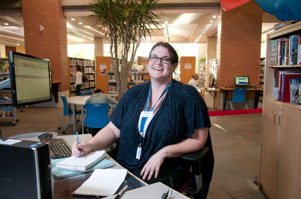 smiling woman sits behind a desk at a library