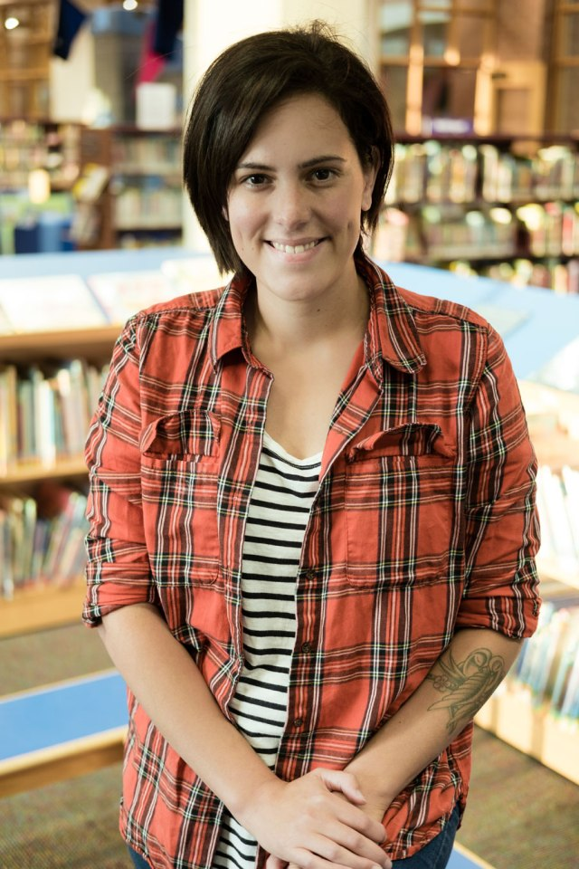 young woman, short dark hair, orange, black and white plaid shirt, striped black and white shirt underneath, standing in library