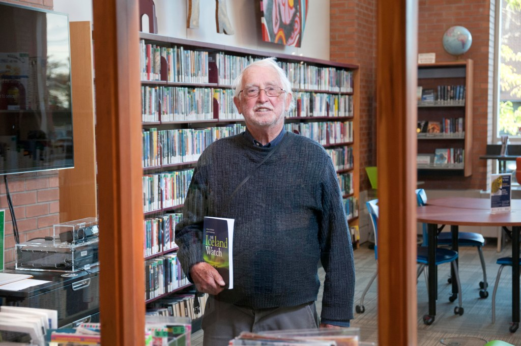 older man in the library holding a book