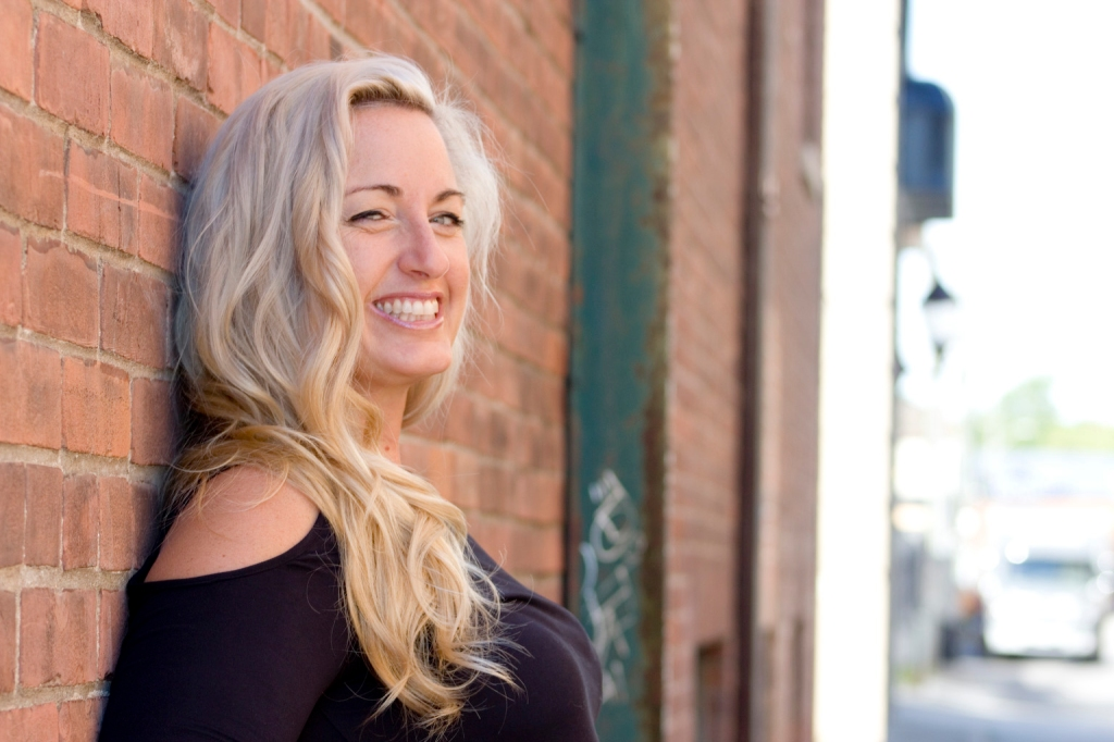 laughing woman with long blonde hair leans against red brick wall