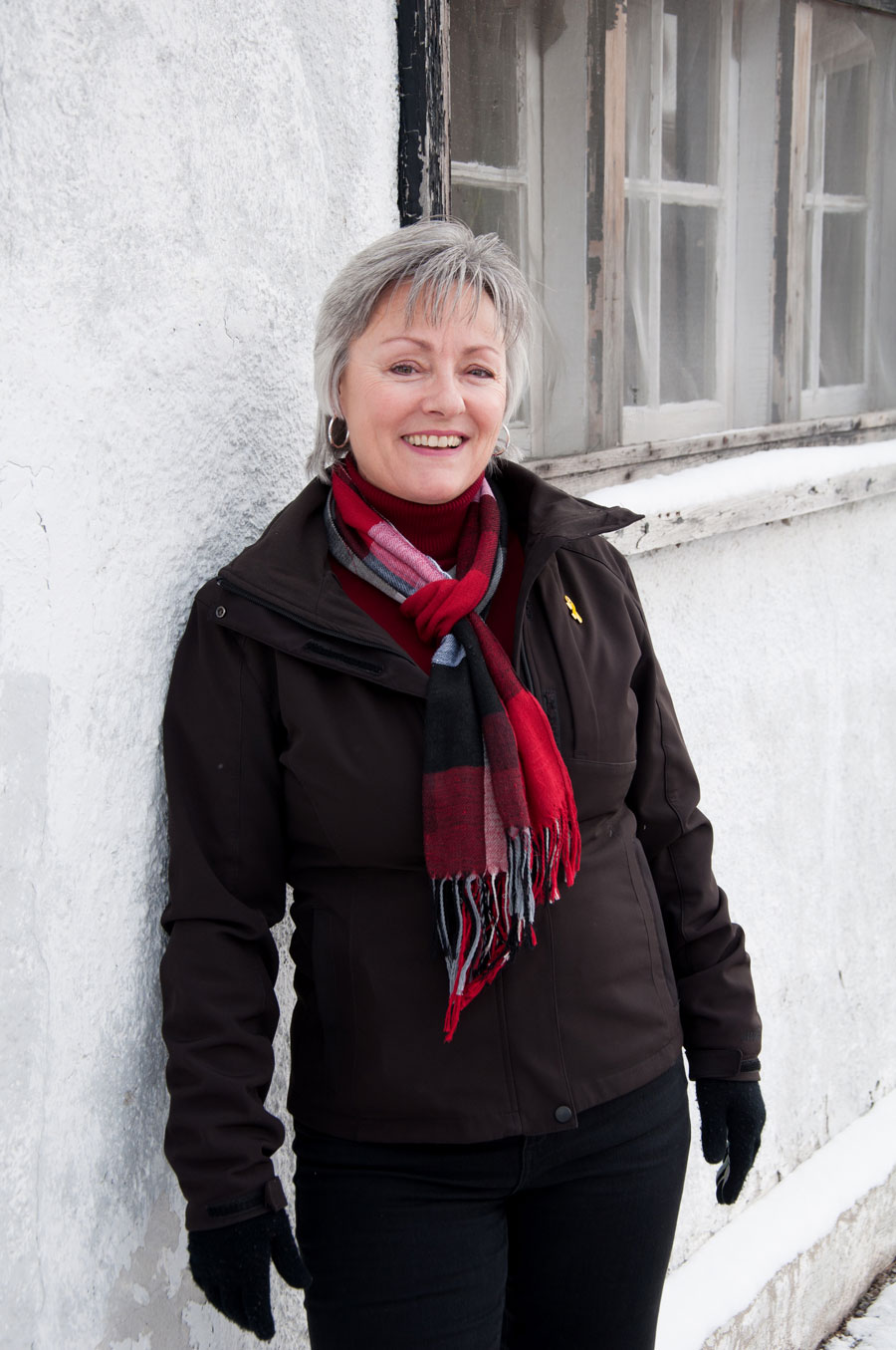 woman in black jacket, plaid scarf, short grey hair, leans against white wall outdoors