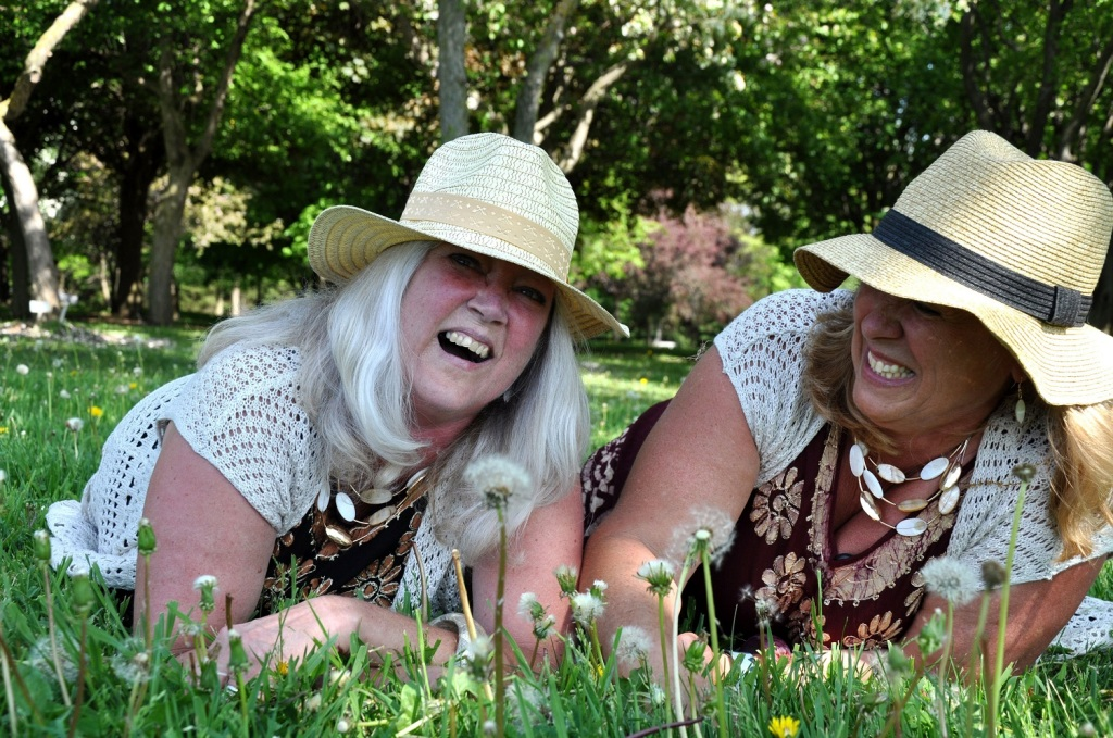 two sisters laying in the grass laughing, both wearing big floppy hats and floral tops
