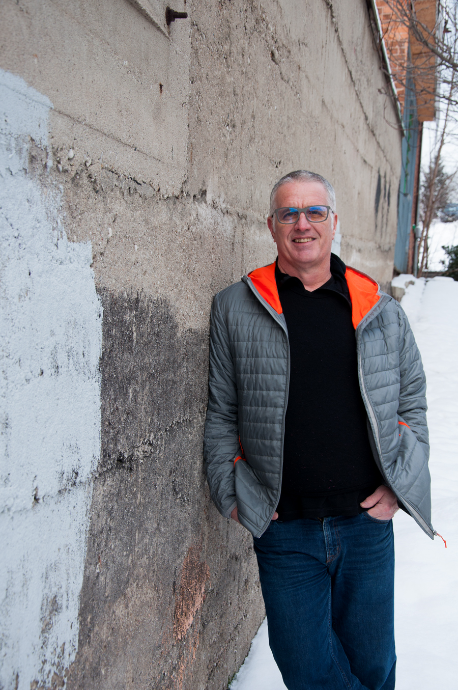 man in jeans, black sweater and grey and orange jacket, wearing glasses, leans on wall outside, downtown alley