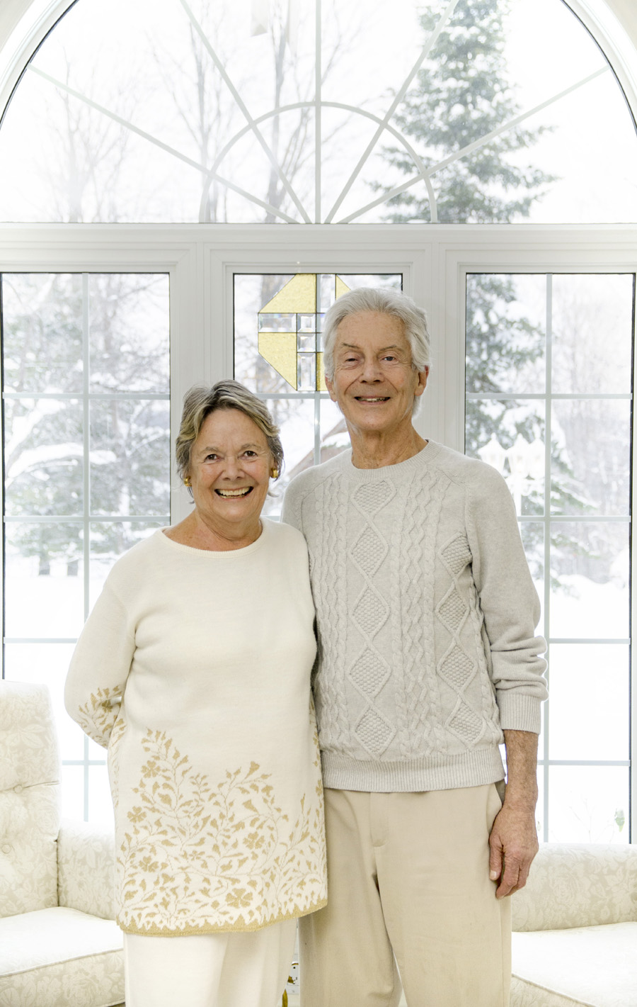 older couple, both wearing white and standing in their livingroom