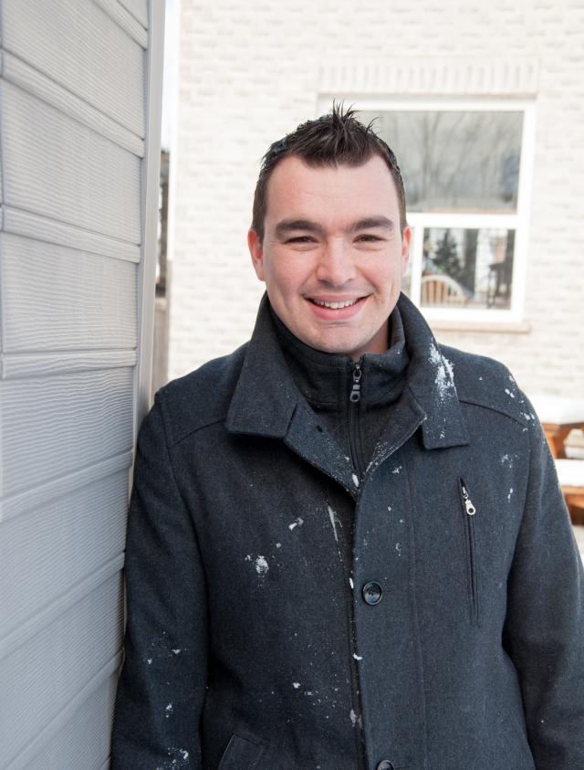 young man outdoors in his backyard wearing black dress coat