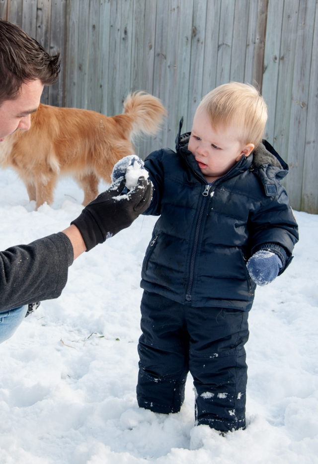 father bends down to give young son a snowball