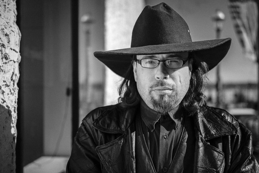 black and white of man wearing cowboy hat and leather coat; head shot with glasses