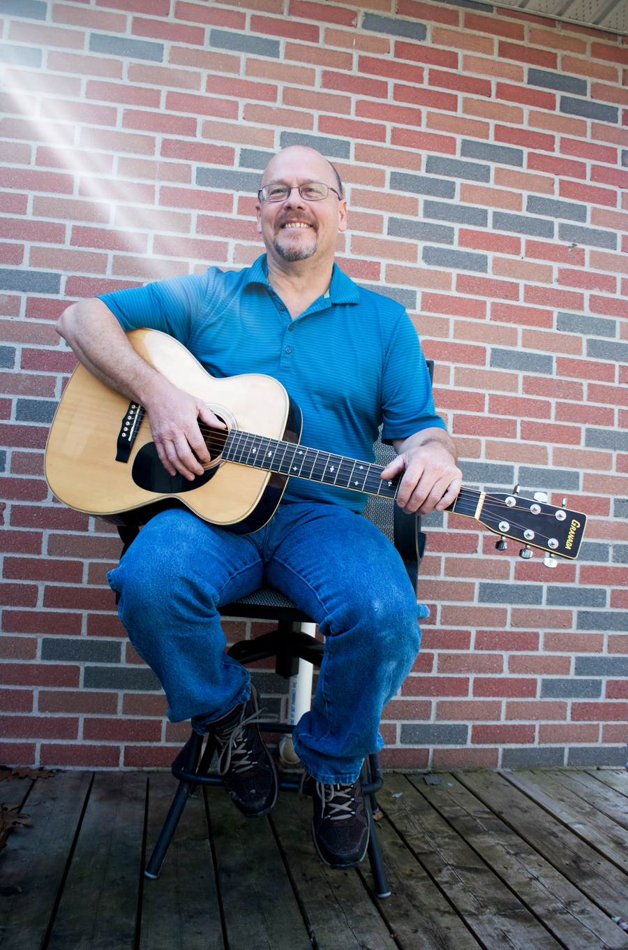 man in blue shirt and blue jeans on a stool on wood deck playing guitar, ray of sun shining on him