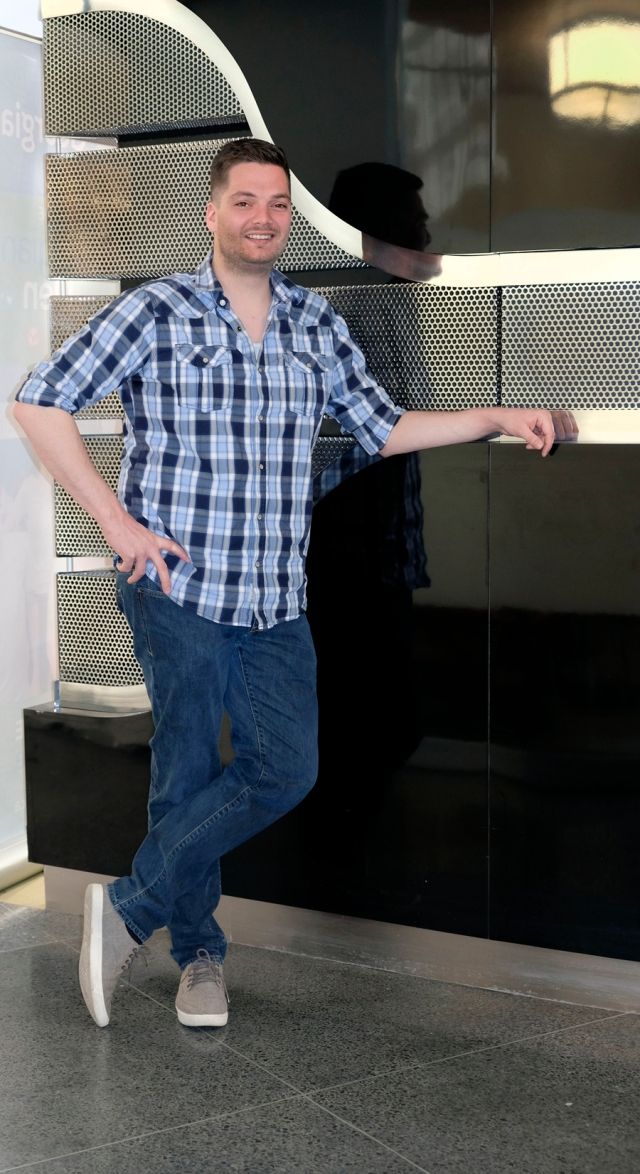 young man in blue plaid shirt and jeans leans against black wall