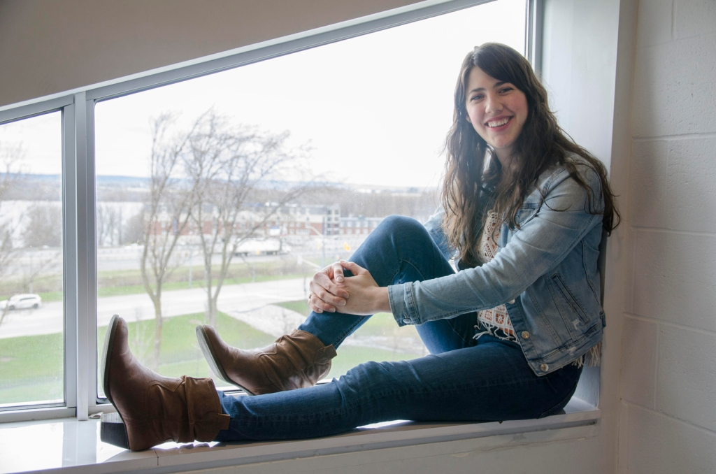 young woman with long dark hair sits in window smiling wearing jean jacket, jeans and brown boots