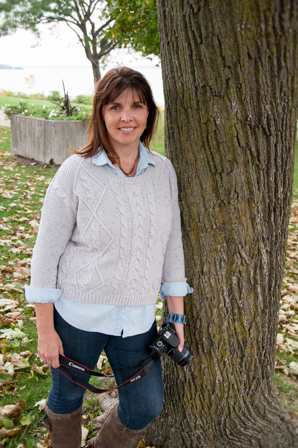 woman leaning against big tree holding camera and wearing grey sweater, blue jeans and brown boots