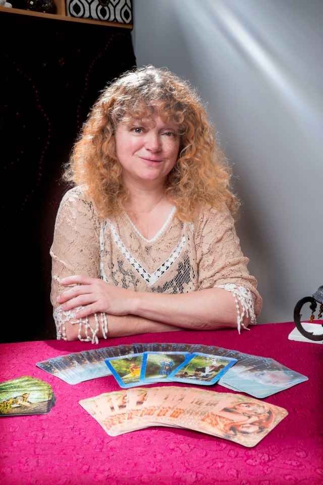 Woman with curly hair sits at table, tarot cards around her
