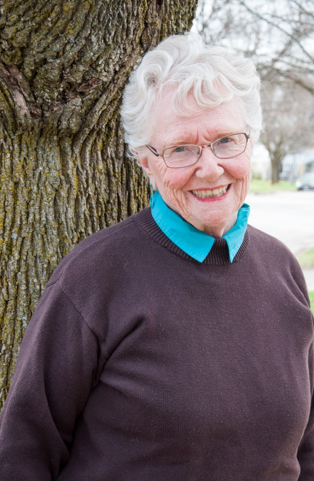 Older woman leans against a tree
