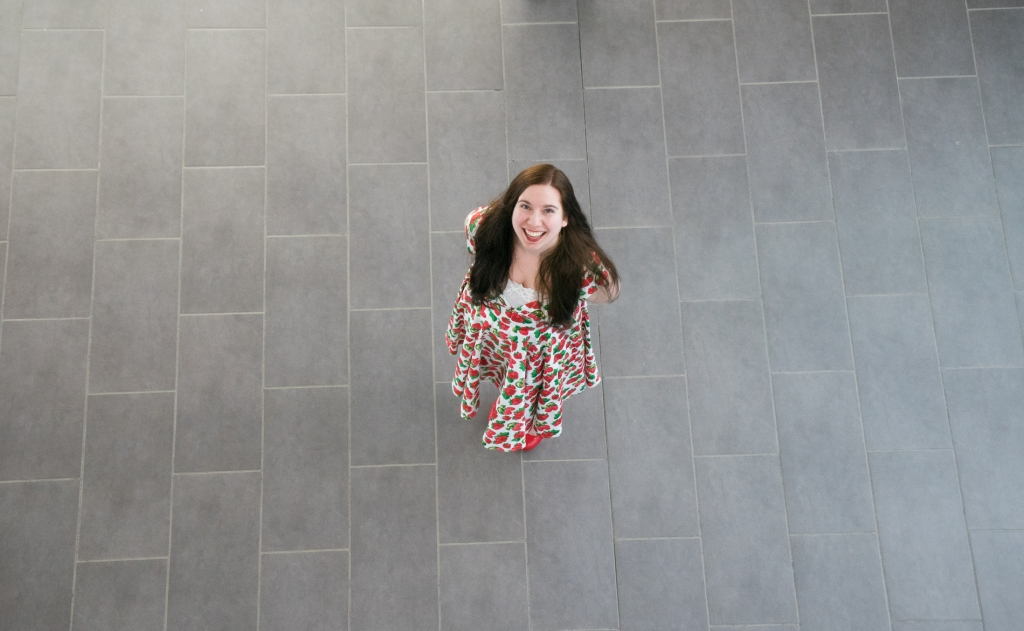 Woman in strawberry dress stands in middle of hallway, aerial view