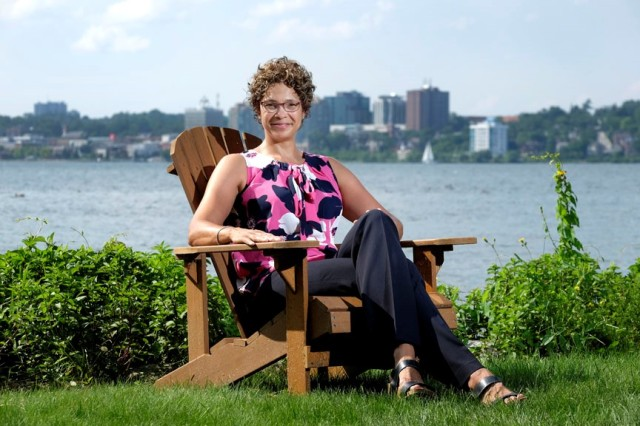 Woman sitting in a Muskoka chair by Kempenfelt Bay
