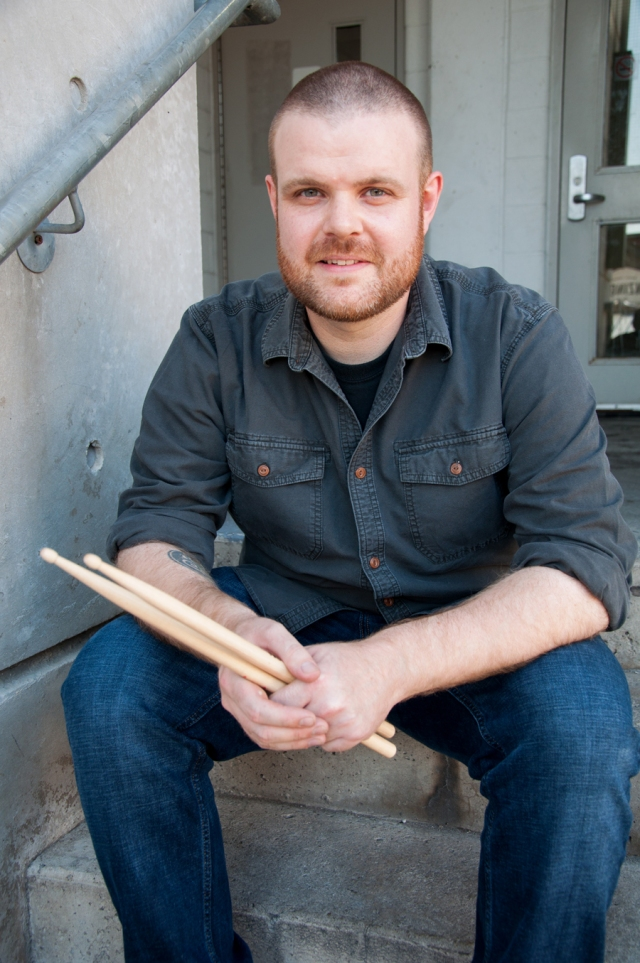 man sits on steps, wearing jeans and long sleeve collar shirt, holding drum sticks