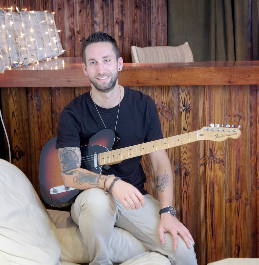 Man with black t-shirt, beige pants, holds guitar, sitting on couch, wood bar behind him