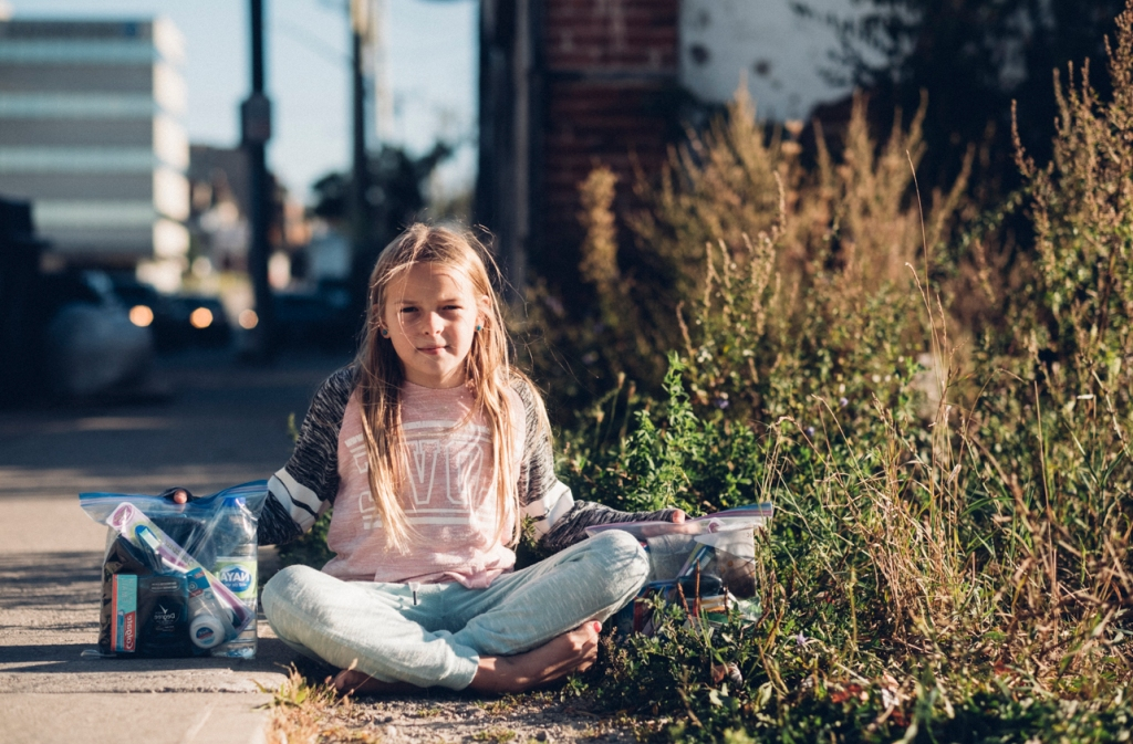 young girl sits on streets downtown; blonde hair, blue jeans, pink tee and sweater, holding up backs of hygiene essentials for the homeless