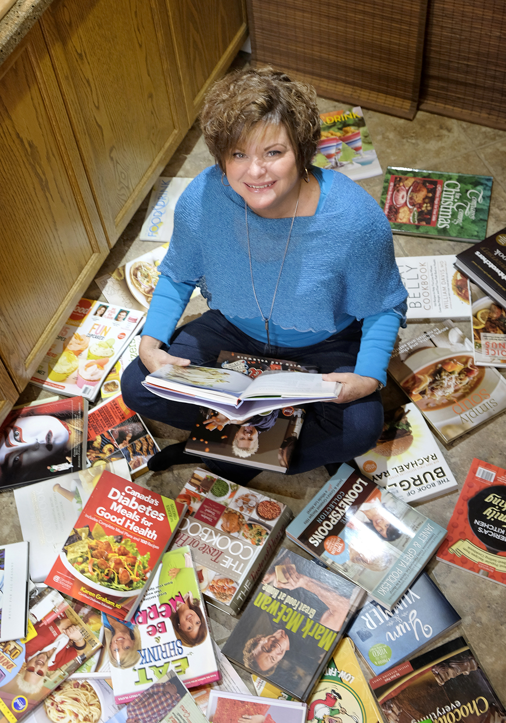 woman with short hair, blue long-sleeve shirt and jeans sits in middle of kitchen surrounded by cook books