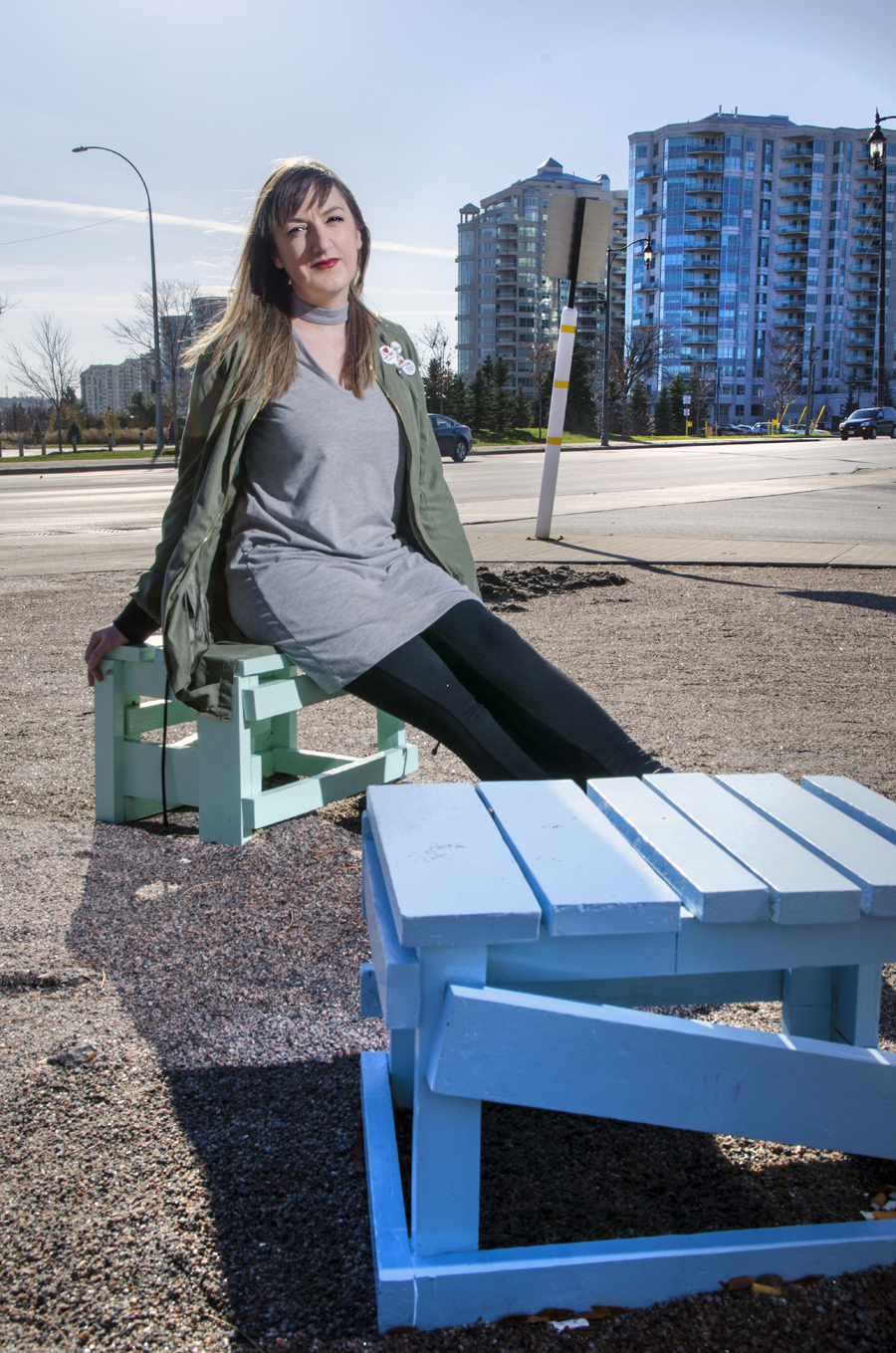 Young woman sits on brightly coloured stool downtown, condos behind her