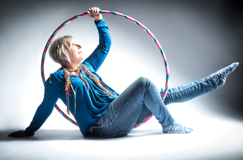 woman in blue shirt and jeans on floor with hoola hoop looped around her, looking at sky