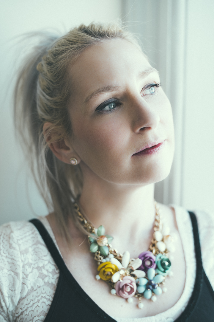 young blonde woman looks pensively out a window, wearing big flower necklace