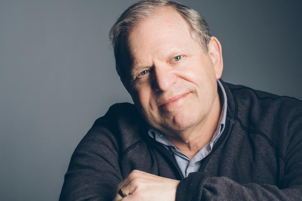 headshot of man sitting down, smiling, wearing sweater