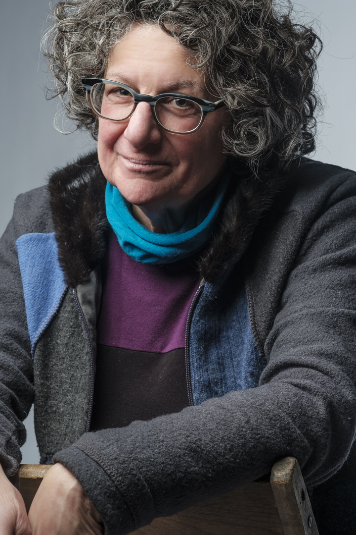 older woman with grey curly hair sits in a chair, glasses, looking fierce but kind