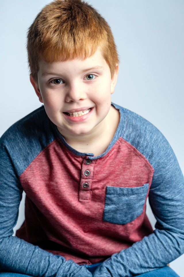 young boy, red hair, blue and red top, one blue eye and one brown