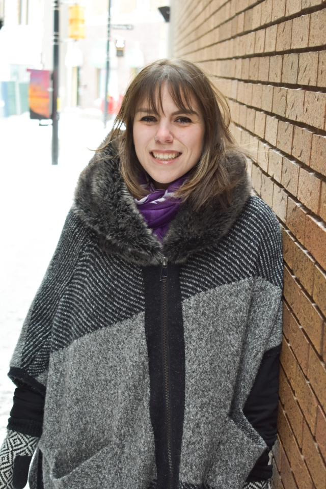 young woman with medium-length brown hair and winter poncho leans against brick wall